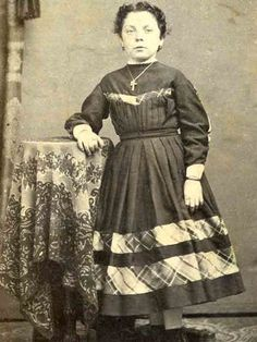 Young lady in solid dress with bands of plaid at bottom of bodice yoke, down sleeve and on skirt.  Lovely accessories.