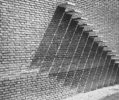 """Effet de lumière sur les abouts de marches """"Bâti au-dessus d'anciennes carrières, sur un terrain remblayé, l'édifice exigeait, par sa masse imposante, des fondations spéciales. La construction repose donc entièrement, par l'intermédiaire de longrines en béton armé, sur 14 puits établis sur le bon sol, entre 4 et 5 mètres de profondeur."""""""