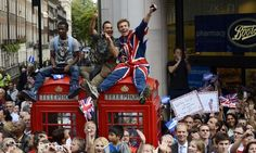 Men wave to the athletes from the top of phone boxes as they watch the parade.