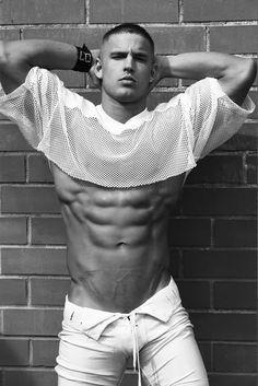 Model Steve Kuchinsky wearing white football pants and a white mesh football jersey