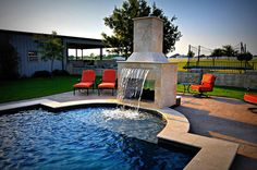 Beautiful backyard pool with water feature and fireplace by Puryear Custom Pools,