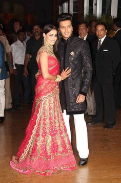 Genelia looked every bit the blushing bride in a paneled red lehnga with a chunky choker necklace. Flowing hair and subtle makeup completed her reception look.