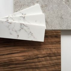 Bianco Drift (grey) Caesarstone, with walnut tone flooring and off white cabinets.