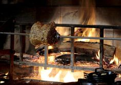 A rack of Pork cooks on the wood fired rotisserie at Cotogna Restaurant