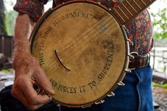 "Mr. Pete Seeger with what became his signature instrument, the 5-string banjo. The well-worn face of Mr. Seeger's banjo was decorated with the message, ""This machine surrounds hate and forces it to surrender."" The banjo head  was donated to the Rock and Roll Hall of Fame and Museum in Cleveland in 2010."
