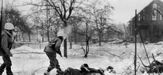 American troops cautiously advance to the bodies of several German soldiers who died during the battle on the outskirts of Jebsheim.
