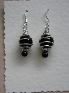 Sterling Silver ear wires with a silver plated cage containing a black glass pearl and a black pressed jet bead finishes the base.