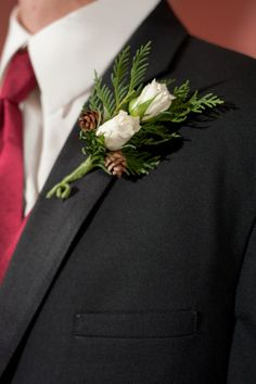 Groomsmen wearing white rose, pine cone and pine boutonniere for a winter wedding