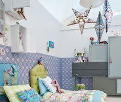 Quarto de criança com decoração eclética. Luminárias de estrelas, cabeceiras, travesseiros coloridos, papel de parede e nichos organizadores.