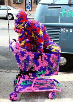 A performer poses in a crocheted shopping trolley, 2011