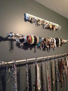 Une idée élégante de rangement Utiliser des tringles à rideaux avec un support mural avec crochet pour ranger tous vos bijoux.
