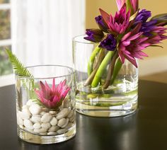 Beautiful decorative flowers placed inside whiskey glasses with water and pebbles