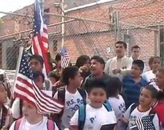 """On Monday, a group of about 20 children got a lesson in political speech when they were heckled by adults as they waved small flags and sang Lee Greenwood's patriotic song, """"God Bless the U.S.A.""""    The children, some of whom were banned from singing the song at their graduation earlier this month, were led by Congressman and U.S. Senate hopeful Bob Turner (R-NY), who held a press conference adjacent to the school that banned the song."""