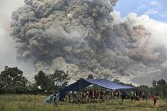 Villagers watch as Mount Sinabung erupts in Perteguhan, in Indonesia's North Sumatra province.