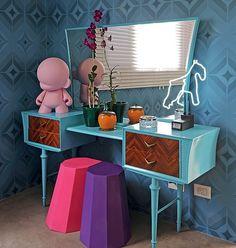 A peteadeira retrô ganhou um ar inusitado com a tinta azul. A toy art e o neon deixam o móvel moderno e divertido