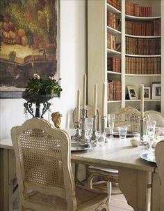 En närmare titt på det dukade matsalsbordet: Strama tenntallrikar och silverljusstakar blandas med e...