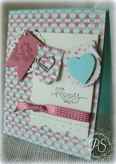 Penny uses Hearts a Flutter & its framelits, Oh Hello, Bloomin' Marvelous (SAB), More Amore dsp, Needlepoint Border embossing folder, & Cute Clips for her cheerful card.