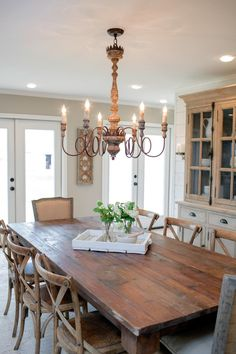 A large farm table, mix-and-match chairs and an impressive chandelier combine the rustic and the elegant to define the new dining space.