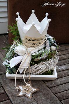Hier seht ihr ein Holztablett auf dem ein Kränzlein liegt, in dem eine Krone als Kerzenhalter sitzt. Ausdekoriert mit verschiedenen weihnachtlichen Accessoires ist die Deko ein echter Blickfang....
