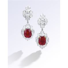 A Rare and Exceptional Pair of Mogok Ruby and Diamond Pendent Ear Clips, Bulgari. Each suspending on an oval ruby weighing 7.80 or 7.10 carats, surrounded by pear-and marquise-shaped diamonds, surmounted by oval, pear- and marquise-shaped diamonds; the diamonds altogether weighing 19 carats, mounted in platinum and 18 karat yellow gold.