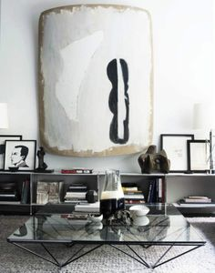 A painting celebrated as a focal point, low shelving holding sculpture & art, and an architectural glass table ...good house soup (bones).