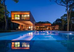 This fascinating modern cantilevered cabin from Tamara Eaton Design features wood both inside and out, as well as a pool, patio and screened porch.