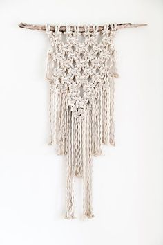 This beautiful modern macrame wall hanging is made from thick natural cotton rope on a piece of driftwood.