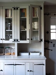 """John McKinney's Bewitching Old Stone House in the Hudson Valley   """"Cabinets on the Kitchen's southern wall. On the lower right are two early Abercrombie & Fitch sandwich tins. All white dinnerware from Fishs Eddy."""""""