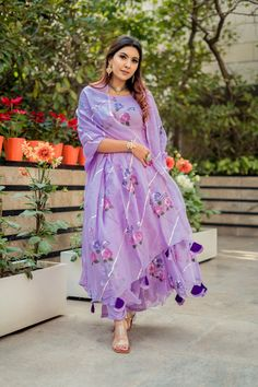 This beautifully handcrafted lilac handpainted suit set is a must have for this spring as it comes with floral handpainted organza anarkali along with satin pants and organza dupatta Dress Indian Style, Indian Dresses, Indian Outfits, Pakistani Fashion Casual, Indian Fashion, Ethnic Fashion, Simple Kurta Designs, Dress Design Sketches, Embroidery Suits Design