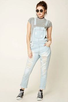 A pair of denim overalls featuring a destoryed design, five-pocket construction, adjustable straps, and snap buttons.