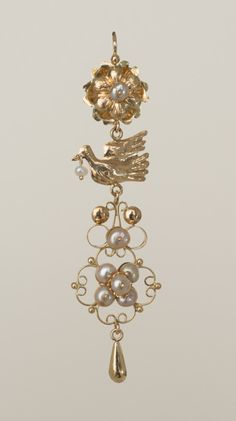 PALOMA CON CEREZO  A charming repoussé dove dangles a cherry from his beak in this traditional earring in 18kt gold and champagne freshwater pearls.