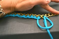 threading fabric onto chain with what looks like a blanket stitch