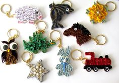 mini quilling ideas to use as keyrings - The basic shape is wood, and on top the quilled interpretation of the animal or shape . When the glue dries they are very stronge and useable.