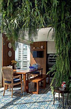 O jardim vertical rouba a atenção nesta varanda projetada pela arquiteta Selma de Sá Moreira. A vegetação se soma ao azul e à madeira, que dão ar de casa ao apartamento. O piso é de ladrilho hidráulico: