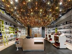 The ceiling of this wine shop consists of a canopy of glass vessels. The light breaks in them like candle light reflected through a glass.