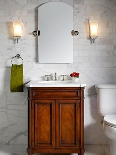 Pretty and Petite - elegant finishes max out the style and feel like the walls and floors done in richly veined marble, small vanity but it is deeply grained and beautifully stained, mirror with lovely arched top