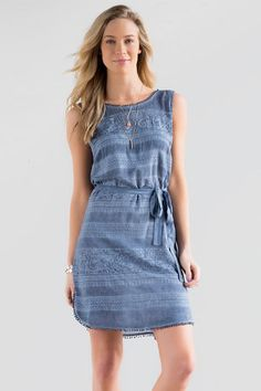 """Take a stroll in the Jolene Embroidered Dress. Subtle embroidery decorates this soft chambray shift dress trimmed with pom pom's & finished with a tie around the waist.<br /> <br /> - 35"""" length from shoulder to hem<br /> - 38"""" chest<br /> - 45"""" sweep<br /> - measured from a size small<br /> <br /> - 100% Rayon<br /> - Hand Wash<br /> - Imported"""