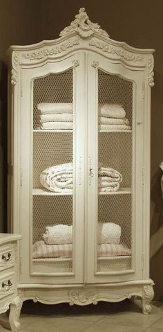Beautiful armoire with wire mesh doors - I have one of these in one of my bathrooms = love the look and functionality