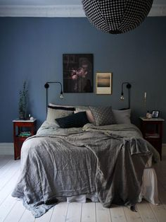 Dark and moody bedroom with navy blue painted walls, dark gray bedding, a mix of gray and black throw pillows, matching cherry wood pedestal nightstands, wall mounted blackened bronze industrial-style sconces and a bright white painted wood floor.