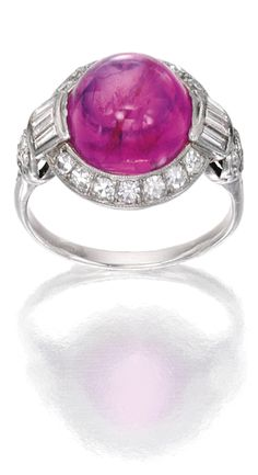*PLATINUM, PINK SAPPHIRE AND DIAMOND RING Centered by a cabochon pink sapphire weighing approximately 9.90 carats, accented by baguette and single-cut diamonds weighing approximately .65 carat, circa 1930.