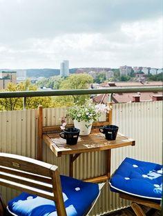 aménagement-balcon-chaises-et-table-plinate-en-bois-tasses-de-café-noirs-fleurs-rose