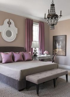 Purple and gray bedroom features walls painted warm gray lined with a dark gray bed dressed in gray bedding and purple pillows next to a gray desk as nightstand and purple round back topped with a silver double gourd lamp.