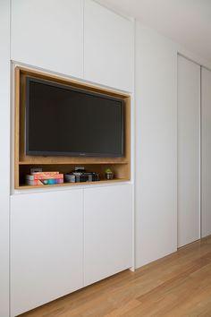 Decoração de apartamento com madeira para dar aconchego. No quarto armário branco com nicho de madeira com tv e adornos.