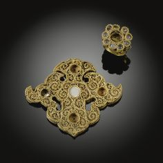 A FINE AND RARE GOLD FILIGREE PENDANT AND GOLD RING, GOLDEN HORDE, 14TH CENTURY    the pendant in the form of a cloudcollar decorated in gold openwork filigree with five round grooves for previously mounted stones, the ring in the shape of a flowerhead, the petals composed of round glass balls with a filigree border  Quantity: 2  6.7cm. pendant  2.5cm. ring
