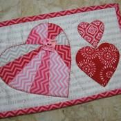 Heartthrob Mug Rug - via @Craftsy. Turn it into a quilt and use butterlies instead of the hearts. The 3 butterflies and smaller ones spread around with hearts, tulips, daughter silhoutte, etc. You get the pic.