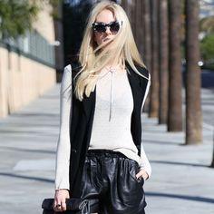Look calça couro, blusa branca e colete.