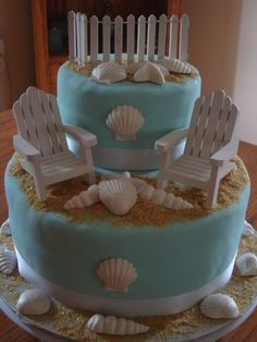 Beach Themed Bridal Shower Cake - Beach themed bridal shower cake.  Shells are white gumpaste painted with white pearl dust.  Fence and chairs are purchased and are wooden.  Sand is a 50/50 mix of sugar in the raw and graham cracker crumbs.  Couples intitiials and a heart are written on fence with fine point marker.