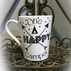 Start out your camping trip with this handmade camping coffee cup. This one happy camper coffee cup is hand embellished with the funny quote in the vinyl graphic shown above. If you would like the saying in any color other than the colors shown above please feel free to use the drop down menu to choose your color. Great gift for the happy camper in your home!    Each white ceramic coffee mug holds 14 ounces and are top rack dishwasher and microwave safe.    Each custom coffee mug we design…