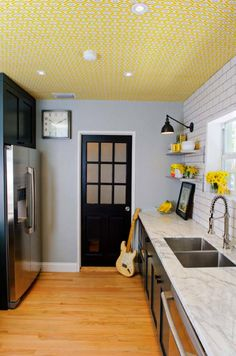 They used a yellow and grey geometric wallpaper from Jonathan Adler for the kitchen ceiling!