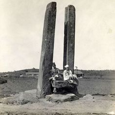 """ca 1920-30s. Two men sit atop """"anchor stones"""" in fields outside Pyongyang. In Korean folklore, Pyongyang is a boat floating in the waters of the Taedong and Potong rivers; some interpretations claim the two great stones moored the city, preventing it from floating away, while others maintain that the monoliths served as masts for the """"floating island city."""""""